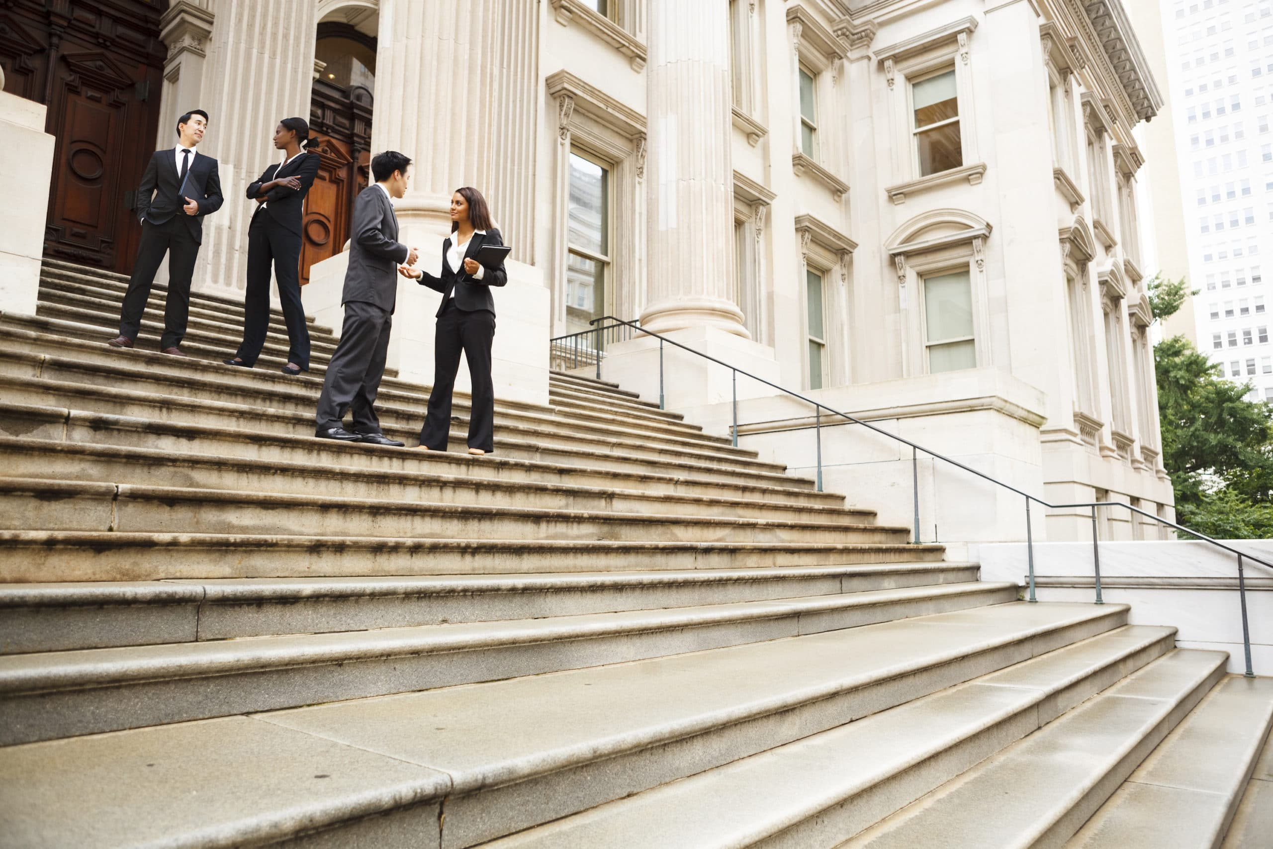 Appellate Lawyer concept. Four well dressed professionals in discussion on the exterior steps of a building. Could be lawyers, government workers, business people etc.